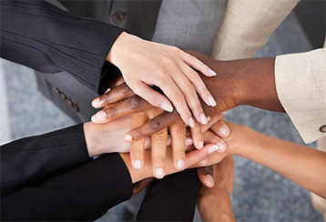 Many hands of different ethnicity stacked on top of each other